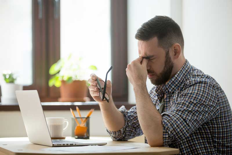 Hombre frente el ordenador cansado y con la vista cansada