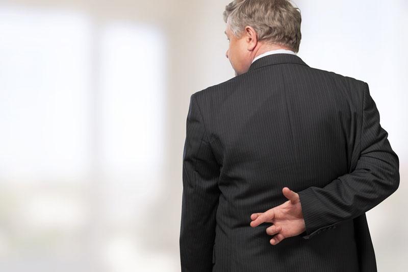 vendedor de software cruzando los dedos por la espalda