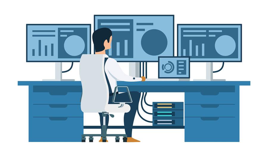 Trabajador frente a un ordenador y múltiples pantallas.