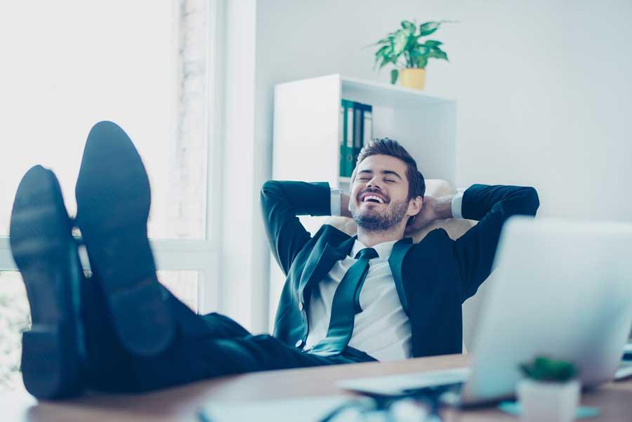 Hombre despreocupado y riendo con los pies sobre la mesa