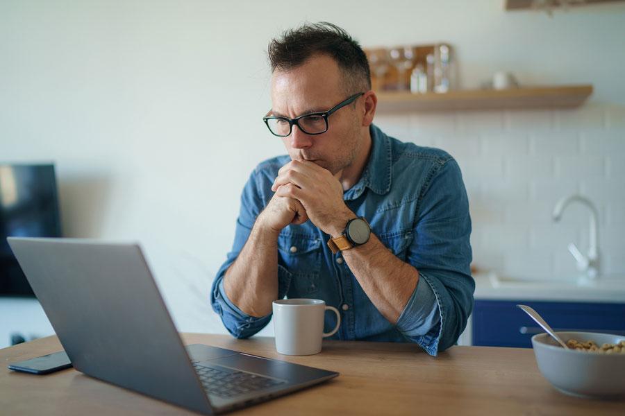 Teletrabajo. Persona en la cocina con laptop.